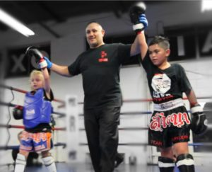 Two muay thai kickboxing athletes getting their hands raised by the ref in their first in house muay thai kickboxing competition at Lanna MMA. Both kids looks exhausted yet proud of their performance.