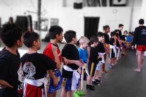 Over ten kids muay thai and martial arts students lining up to bow after their martial arts class. The kids are all dressed in their muay thai kickboxing uniforms.