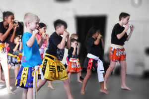 A group of boys and girls ages six to 12 in their muay thai uniforms, working on their muay thai kickboxing techniques in the mirror in their muay thai kickboxing and martial arts at Lanna MMA