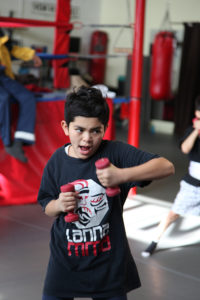 Eight year old boy with short hair and lots of intensity/focus works on punches with light weights in his hands to improve his endurance for muay thai and kickboxing