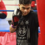 Student working on a left hook on the punching bag during his boxing class at Lanna MMA in North York and Vaughan