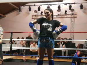Brenda standing proud with her hands on her hips and boxing gloves and elbow pads on , after winning her first sanctioned Muay Thai fight at SheFights.