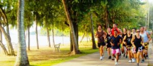 Several muay thai students running together in a tropical setting