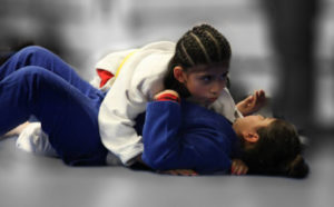 Kid on the bottom in a blue martial arts uniform trying to escape the top kid in a white uniforms cross side pin in brazilian jiu jitsu (bjj) class