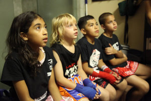 A group of four Muay Thai and Martial Arts students from Lanna MMA sitting next to each other attentively listening to their coaches instructions