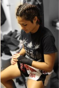 female putting on boxing handwraps sitting down, as she gets ready for her boxing class at Lanna MMA in Vaughan Ontario