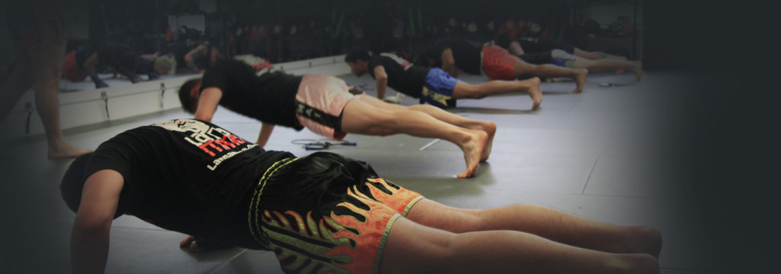 A group of strength and conditioning students doing pushups together as a team at Lanna MMA in Vaughan