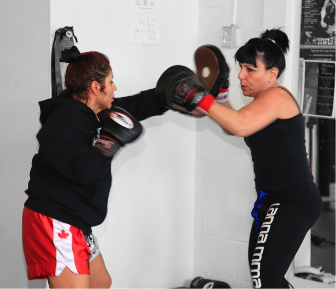 two women holding training together in a kickboxing class at lanna mma in woodbridge. One woman is holding the pads for the other woman who is punching
