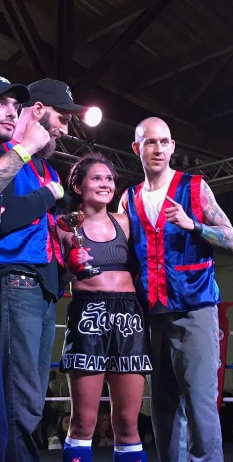 19 year old Female muay thai kickboxing fighter Brenda standing with her trophy and 3 coaches in the ring after winning her fight at the Mitsubishi Cup 2