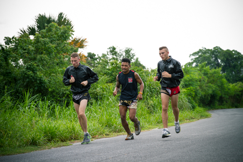 Three muay thai fighters in thai shorts and sweat tops running in beautiful scenery to warm up for their muay thai session
