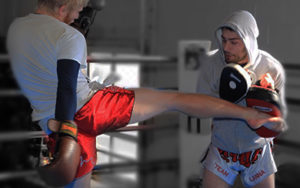 Person kicking and trainer holding the pads while in a boxing ring in a kickboxing class at Lanna MMA in the Vaughan and Woodbridge area