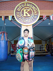 Muay Thai boxer standing in front of gym labelled kaewsamrit holding his championship belts
