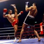 Red corner executing an axe kick on the blue corner opponent in a professional kickboxing fight
