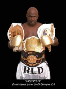 Kickboxing fighter standing with 4 world championship K-1 belts