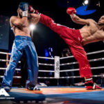 two kickboxing fighters competing in a boxing ring. The fighter wearing red is executing a kick to the head while the fighter in blue is trying to block it