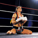 Female Muay Thai fighter bowing in a boxing ring with traditional muay thai garments and boxing gloves