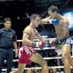 Muay Thai fighter in blue elbowing Muay Thai fighter in red in a Muay Thai Boxing Match
