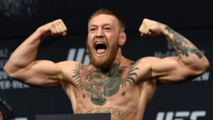 UFC fighter, Conor McGregor flexing his biceps while screaming in excitement. He is standing on a scale at a weigh in prior to his UFC fight